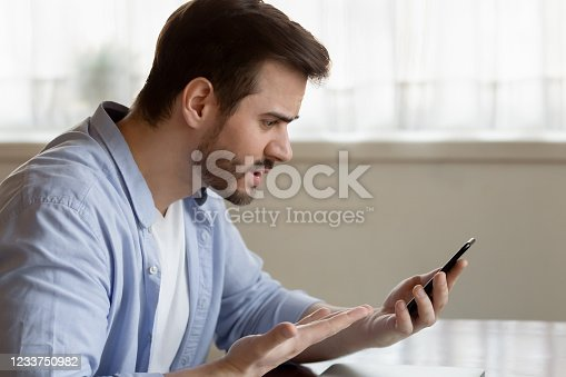 824614192 istock photo Mad young bearded man irritated by scam spam message. 1233750982