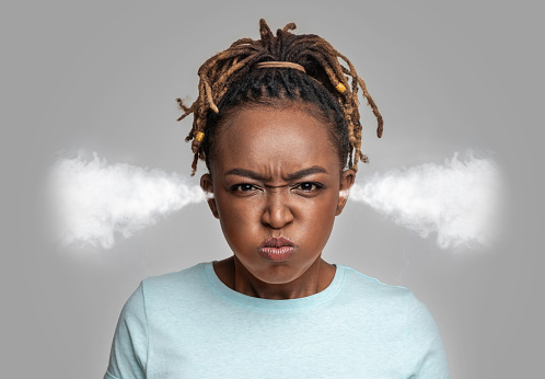 Mad african-american lady has steam coming out of her ears, expressing anger, grey studio background, closeup. Offended black woman with puffy cheeks showing hatred and impatience, negative emotions