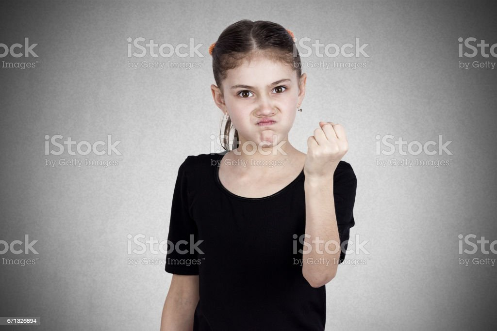 mad young girl about to have nervous atomic breakdown, fist up in air stock photo