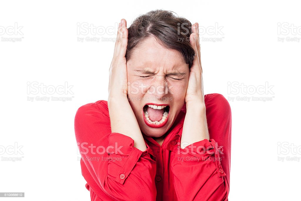 mad young woman screaming, covering her ears to refuse listening stock photo