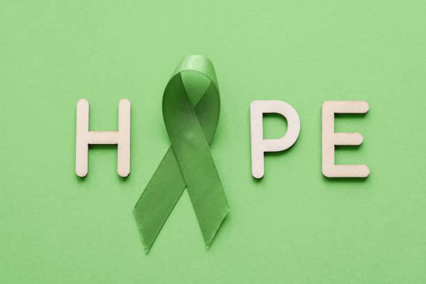 HOPE aus Holzbrief mit Lime Green Ribbon auf grünem Hintergrund, Psychische Gesundheit Bewusstsein und Lymphom Bewusstsein, Welttag der psychischen Gesundheit – Foto