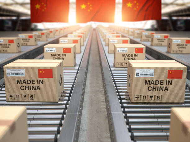 Made in China. Cardboard boxes with text made in China and chinese flag on the roller conveyor. stock photo