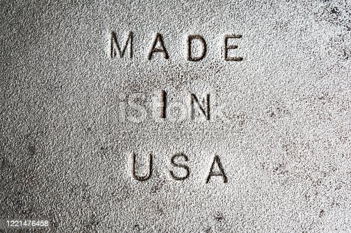 Extreme Close Up of Made In USA embossed not old cast iron. Rough and gritty texture. Perfect for concepts about jobs, out-sourcing, manufacturing, factories, skills, imports, exports and trade balance.