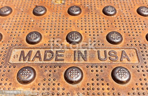 Close up on the words 'Made In USA' on a worn and weathered metal surface.