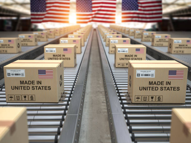 Made in USA United States. Cardboard boxes with text made in USA and american flag on the roller conveyor. stock photo