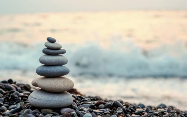 der steinturm auf den strand und unschärfe hintergrund gemacht - gleichgewicht stock-fotos und bilder