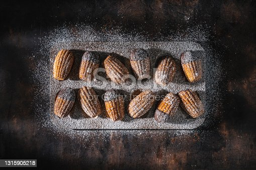istock Madeleines Homemade and melted chocolate on a mold in a row with icing sugar on dark wood 1315905218
