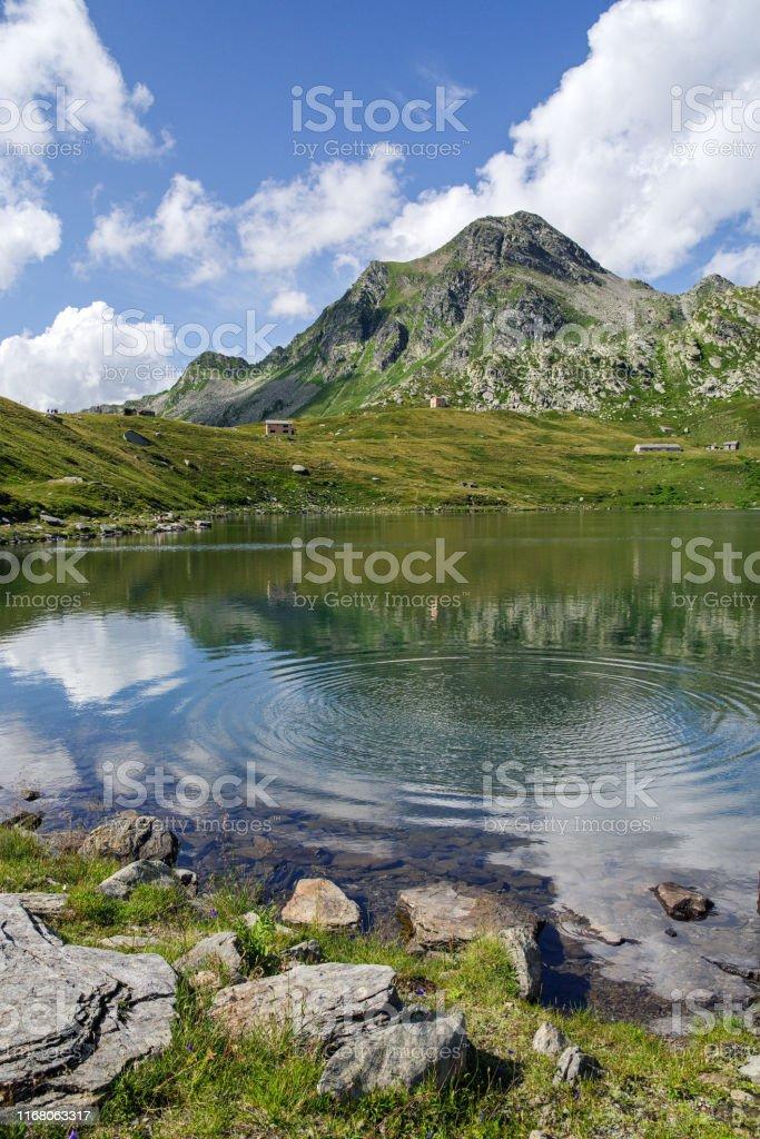 Madesimo, Sondrio, August 8, 2019 - Lake Emet (2145 m), an alpine lake roughly circular with diameter of 300 m, has several small tributaries - Стоковые фото Без людей роялти-фри