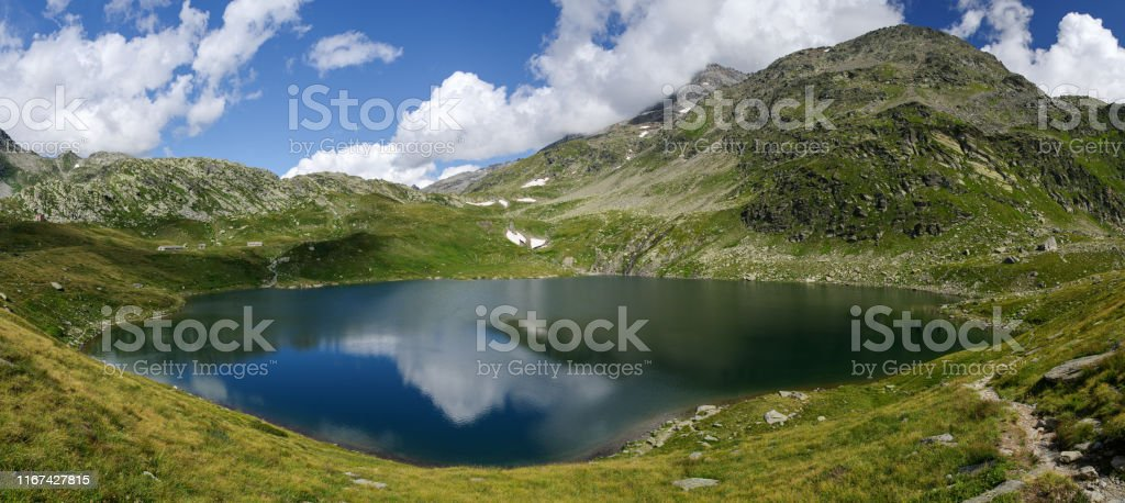 Madesimo, Sondrio, August 8, 2019 - Panoramic view on lake Emet (2145 m), an alpine lake roughly circular with diameter of 300 m, has several small tributaries - Стоковые фото Без людей роялти-фри