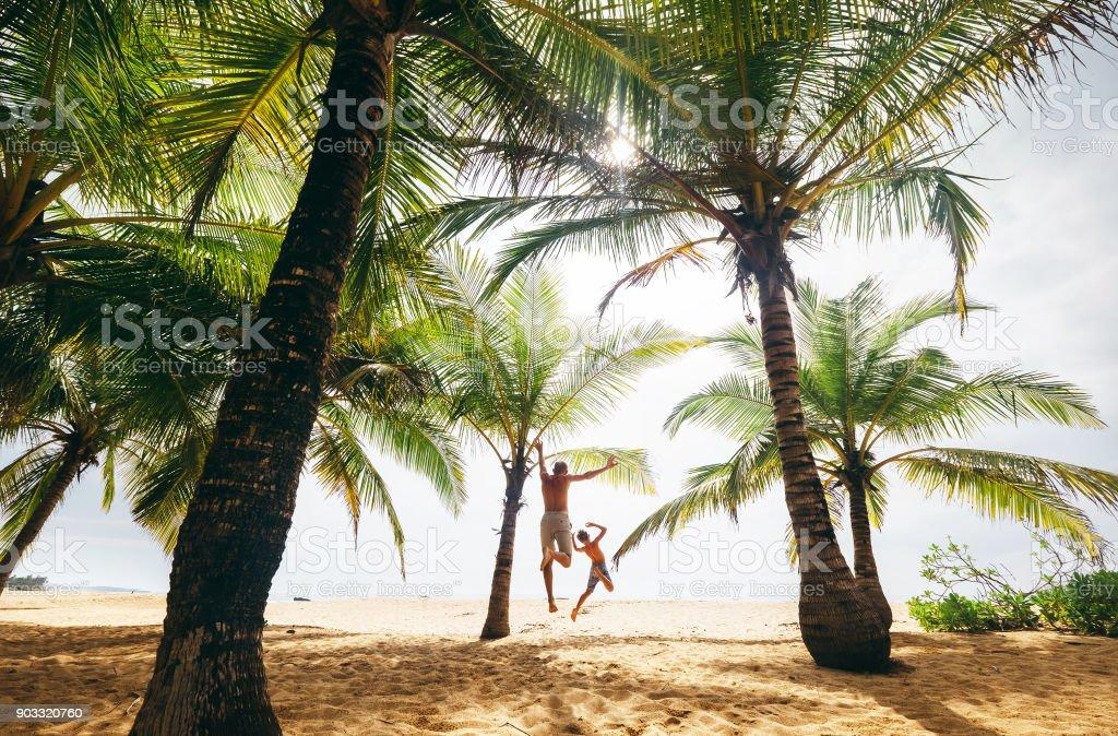 Wie verrückt springt weiter und Sohn auf der einsamen Insel Strand – Foto