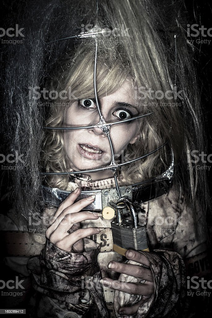 Madness Woman in Straitjacket Horror Portrait Desperate, crazy woman trapped in straightjacket looking weird and crazy with wide open eyes, holding the lock of the metal cage around her head. Spooky, bizarre Madness-Horror Portrait. Adult Stock Photo