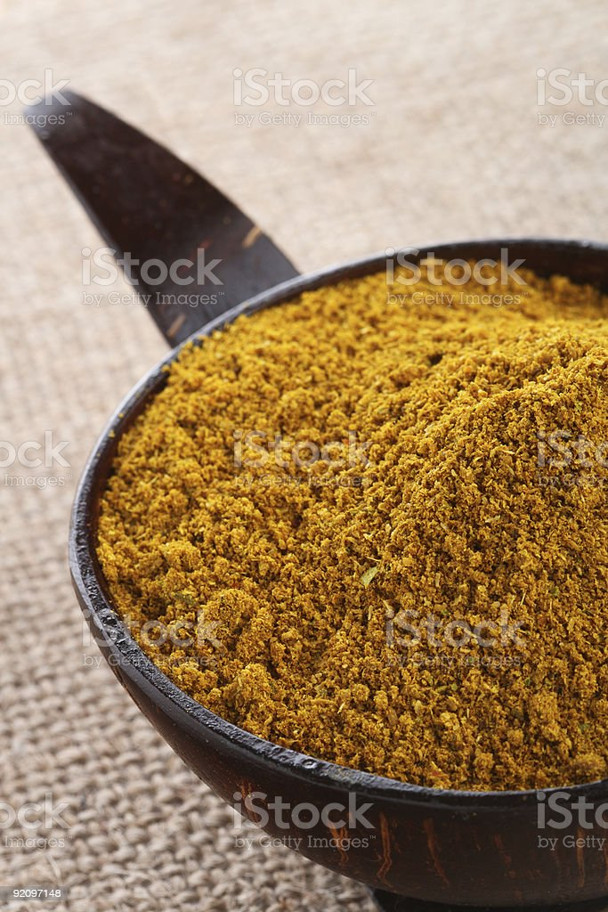 Madras Curry Powder in coconut bowl on hessian background royalty-free stock photo