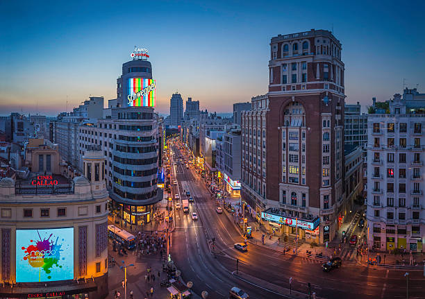 マドリッドの gran via 混雑したショッピング街のランドマーク照明付きサンセットスペイン - マドリード グランヴィア通り ストックフォトと画像