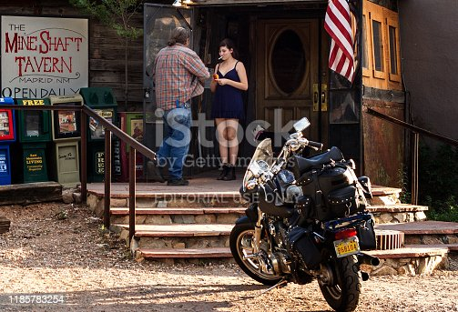 Madrid, NM: A young woman and a man chatting outside a bar at sunset; a motorcycle is in the foreground. Madrid is a village just south of Santa Fe.