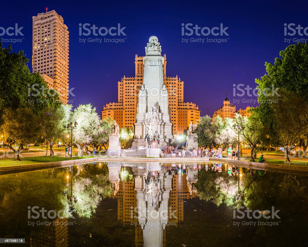 Madrid Plaza de Espana tourists at spotlit Cervantes monument Spain stock photo