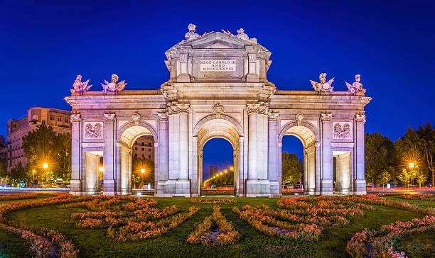 ・プエルタデアルカラ教会象徴的な夕暮れのスペイン王宮門照明付き - マドリード グランヴィア通り ストックフォトと画像