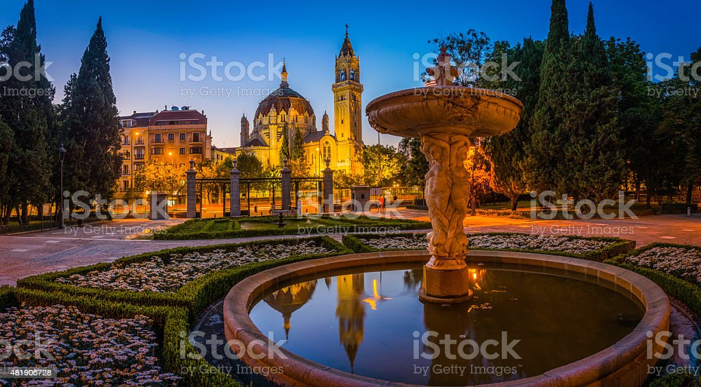 Madrid Retiro Park fountains ornate church towers illuminated dusk Spain stock photo