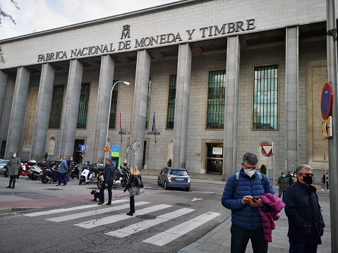 """Madrid, Spain. April 23, 2021: Mature people wearing face protective masks in front of the """"Fabrica Nacional de Moneda y Timbre""""."""