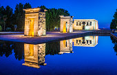 The ancient Egyptian stone pylons of the Temple of Debod, spotlit against the deep blue dusk skies in the Parque del Oeste in the heart of Madrid, Spain's vibrant capital city. ProPhoto RGB profile for maximum color fidelity and gamut.