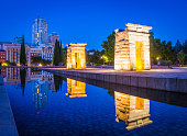 Madrid, Spain - July 10, 2015: Visitors enjoying the warm night air beside the ancient Egyptian stone pylons of the Temple of Debod, spotlit against the deep blue dusk skies in the Parque del Oeste in the heart of Madrid, Spain's vibrant capital city.  Panoramic image created from four contemporaneous sequential photographs.
