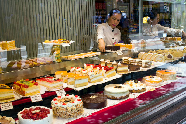 Madrid - Woman set up a pastries window display of La Mallorquina, Puerta del Sol stock photo
