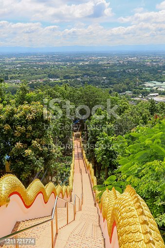 Mae Hia,Chiang Mai,Northern Thailand on Septemmber 13,2019:Golden colored Naga serpents guard the stairs on both sides of the stairway from the ground to Wat Phra That Doi Kham.