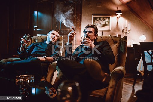 Mafia Family Father And Son Enjoying Good Cognac With Cigars And Conversation