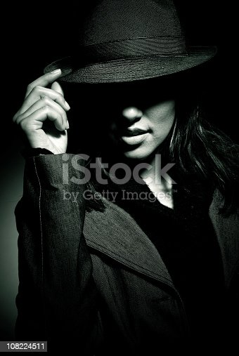 girl wearing black clothes, hat and gabardine - face partially illuminated by a spotlight