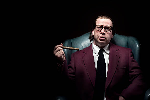 Mafia Mobster A dark brooding business man looks at the camera with an intimidating expression and holding a big cigar.  Horizontal with copy space. gangster stock pictures, royalty-free photos & images