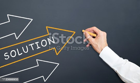 maganer drawing solutin arrows with chalk on blackboard