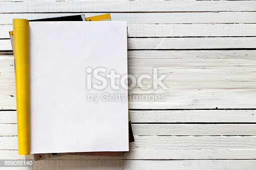 istock Magazine page mock up catalog opened on a white wooden background. Top view. Copy space 899055140