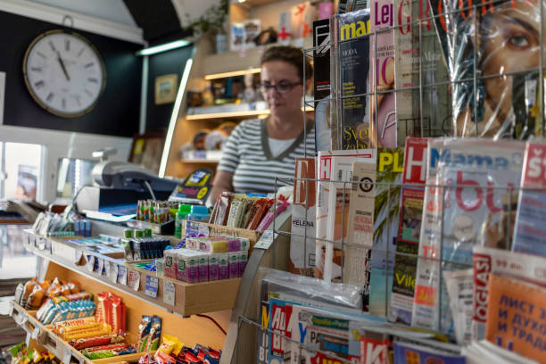 Magazine stand and female seller in a tobacco shop Belgrade, Serbia, June 16th 2019: Magazine stand and female seller in a tobacco shop in Zemun. news stand stock pictures, royalty-free photos & images