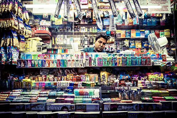 Magazines, candy and snack street shop New York, New York, USA- October 16, 2014: Asian man selling at a Magazines, candy and snack street shop in New York City news stand stock pictures, royalty-free photos & images