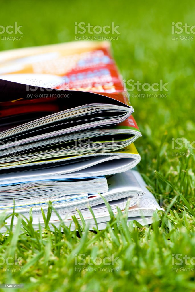 Magazines on green grass royalty-free stock photo