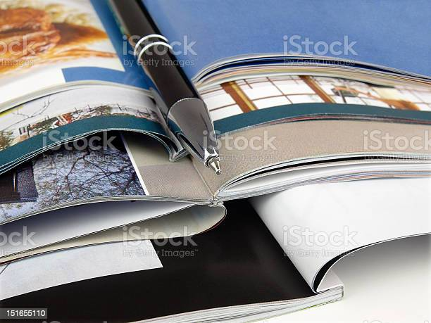 Magazines Open And Stacked With A Pen Stock Photo - Download Image Now
