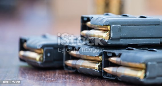 1043434568 istock photo Magazines with bullets of firearm putted on wooden table. Close up view, blurred background. 1033275058