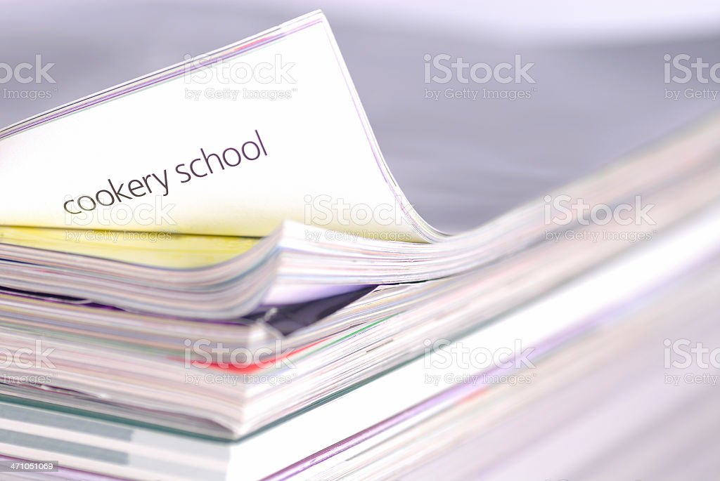 Magazines with page on 'Cookery School' lifted up royalty-free stock photo