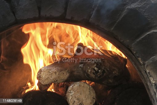 Stock photo of traditional outdoor brick oven cooking homemade pizzas at Italian pizzeria restaurant, brick-built garden wood burning stove bonfire flames, long handled metal pizza paddle shovel.