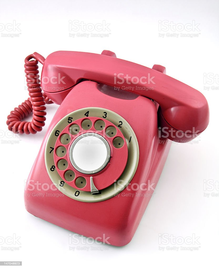 Magenta colored rotary telephone on a white surface  stock photo