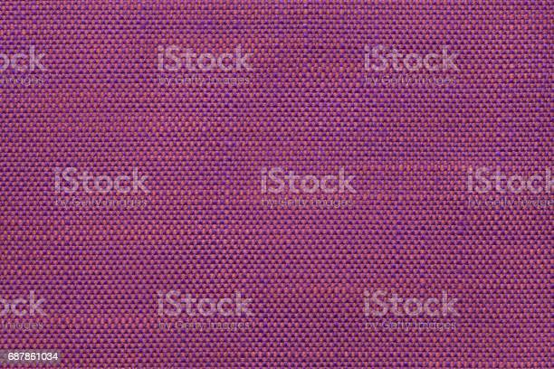 Photo of Magenta textile background with checkered pattern, closeup. Structure of the fabric macro.