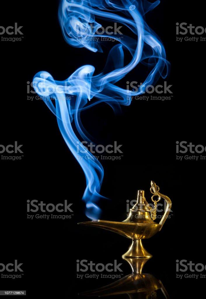 Magic Aladdin lamp with smoke on a dark background stock photo