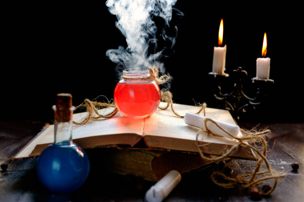 Magic and wizardry concept. Magic and wizardry concept. Set of sorcery book, magic potions and candles on table. Health and mana potion. Alchemy concept. arcane stock pictures, royalty-free photos & images