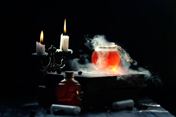 Magic and wizardry concept. Magic and wizardry concept. Set of sorcery book, magic potions and candles on table. Health potion with vapor streaming from bottle. Alchemy concept. arcane stock pictures, royalty-free photos & images