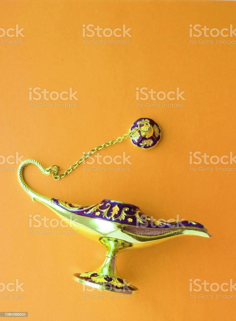 Magic Antique Aladdin Lamp on a beautiful orange background. Close up. flat lay. stock photo