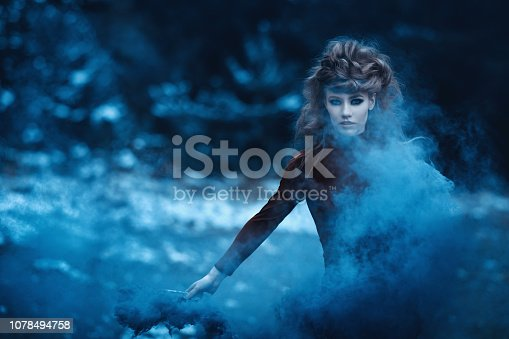 magician woman in the woodland holding flaming torch, surrounded by blue smoke.