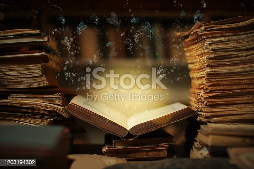 Magical book lying open on desk in library. Fairies from fairy tale flying from glowing pages and illuminates surrounding.