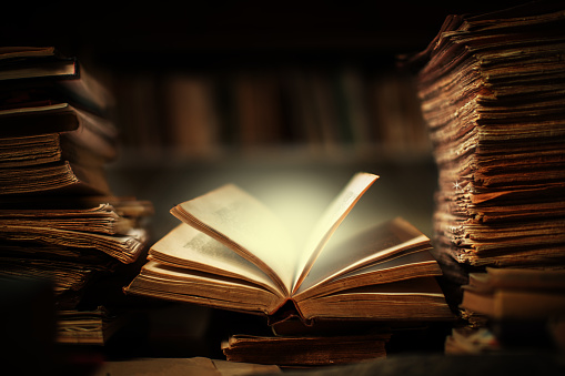 Magical book lying open on desk in library. Glowing pages illuminates surrounding.