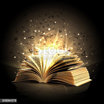 istock Magic book with magic lights and letters 528364379