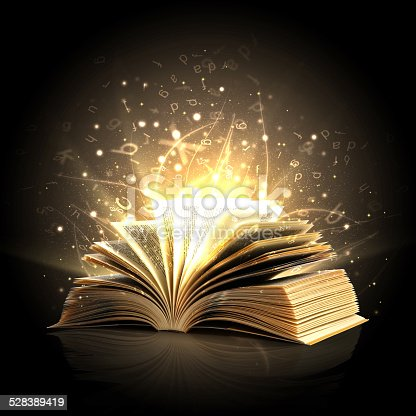 istock Magic book with magic lights and letters 528389419
