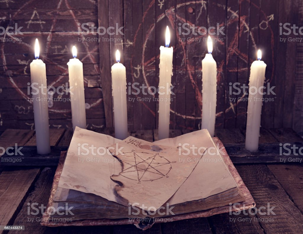 Magic book with pentagram and evil candles for occult ritual stock photo